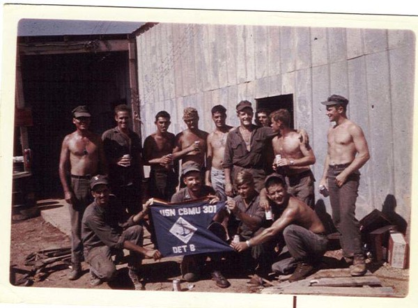 Bruce Morris standing with arm around Mac (Dave McLennon) at Dong Ha after the Siege-PUC ribbon attached to flag