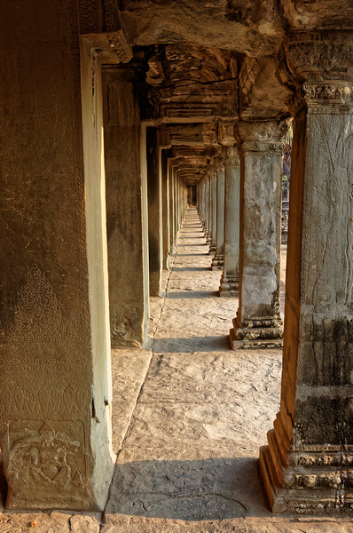 View of a portion of the interior gallery. Note the bas-relief meditating yogi at the base of the column at left: a common motif at Khmer temples.