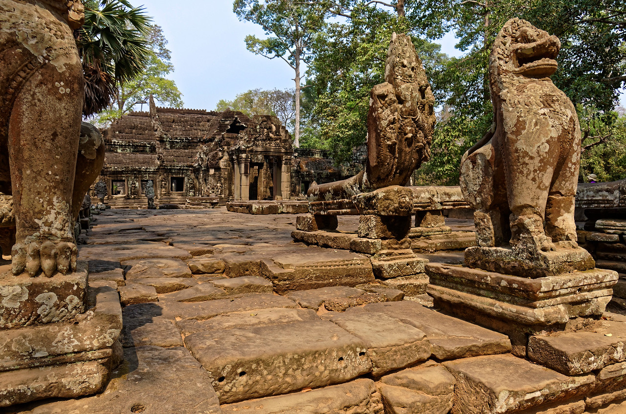 Lions and <i>nagas</i> stand guard at the edges of a terrace leading into the temple buildings.