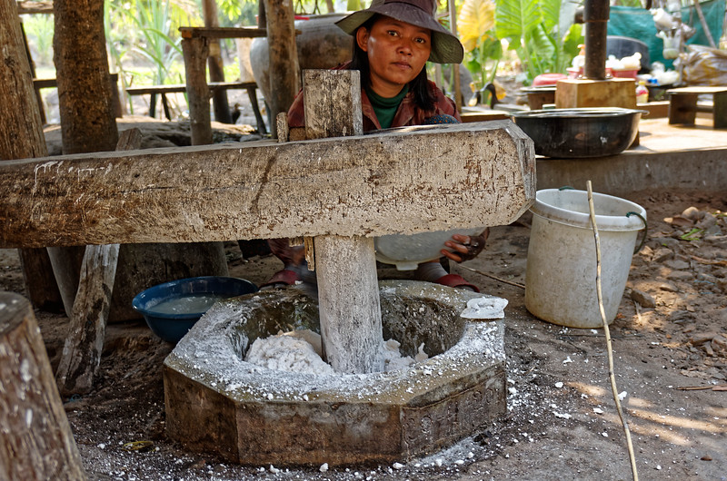 The rice is first soaked until it begins to soften. This woman was adding the softened rice to the little pit, where it was being pulverized by the wooden pounder. Another person operated the pounder by foot.