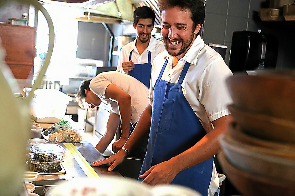 . Kickin Chicken owners Justin Williams, right, and Danny Mendoza, center, and manager Matt Ruhland keep it light and busy in the kitchen at Motiv. (Shmuel Thaler � Santa Cruz Sentinel)
