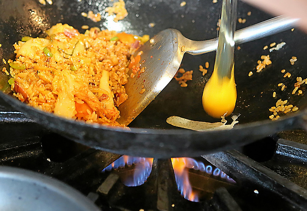 . An egg drops into an order of Kimchi fried rice with bacon being wokked at Kickin Chicken. (Shmuel Thaler � Santa Cruz Sentinel)