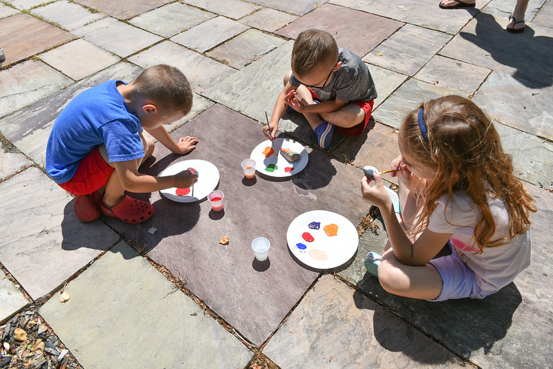 Twin's Matthew (left) and Andrew (center) Sklamon, 4, of Lunenburg paint rocks with sister Kendal, 6, at the Lunenburg Public Library on Monday where kids and their families gather to draw inspirational messages on rocks which are to be displayed in nature throughout the community. SENTINEL & ENTERPRISE JEFF PORTER