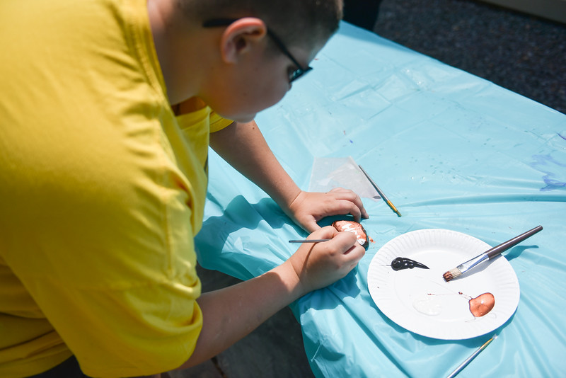 "Tyler Defrancesco, 13, paints a rock with the words ""Friends Help"" at the Lunenburg Public Library on Monday where other kids and their families gather to draw inspirational messages on rocks which are to be displayed in nature throughout the community. SENTINEL & ENTERPRISE JEFF PORTER"