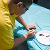 """Tyler Defrancesco, 13, paints a rock with the words """"Friends Help"""" at the Lunenburg Public Library on Monday where other kids and their families gather to draw inspirational messages on rocks which are to be displayed in nature throughout the community. SENTINEL & ENTERPRISE JEFF PORTER"""
