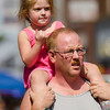 Daphne Pallotta, 3, hitches a ride from dad Jim during Kid's Day in downtown Leominster on Saturday afternoon. SENTINEL & ENTERPRISE / Ashley Green