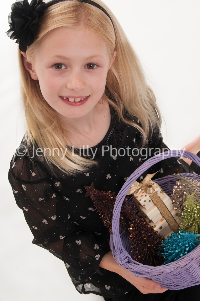 pretty blonde girl with basket, carrying Christmas presents, isolated on white