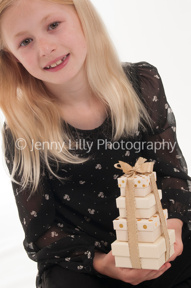 pretty blonde girl holding a stack of Christmas presents, isolated on white background