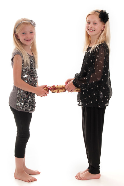 pretty blonde girls pulling a Christmas cracker, isolated on white background