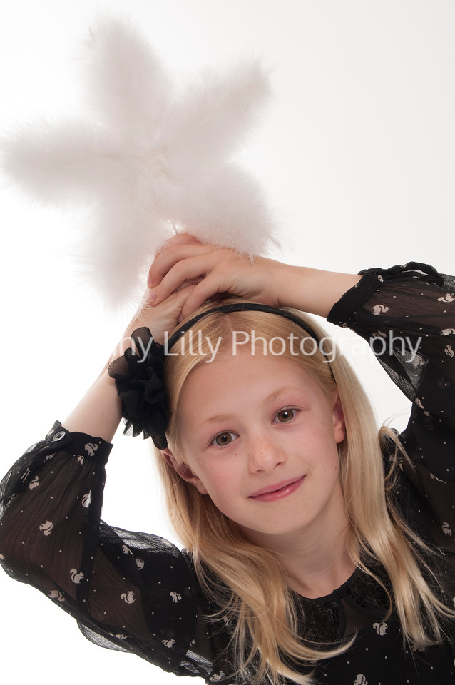 pretty blonde girl with a feather Christmas star, isolated on whtie