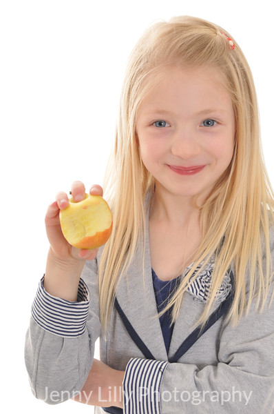 pretty blonde girl eating an apple isolated on white background