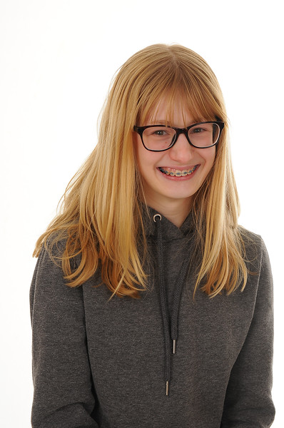 pretty blonde teenage girl wearing glasses and visible braces on her teeth isolated on white background