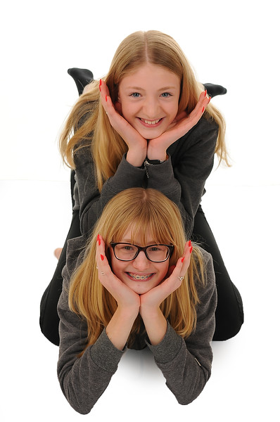 two pretty blonde teenage girls sitting on top of one another isolated on white background