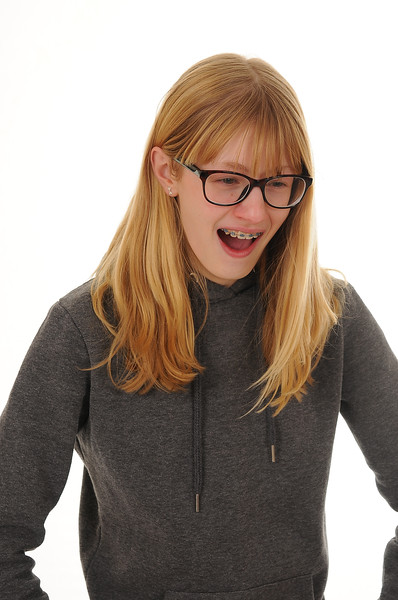 pretty blonde teenage girl wearing glasses and yawning, isolated on white background