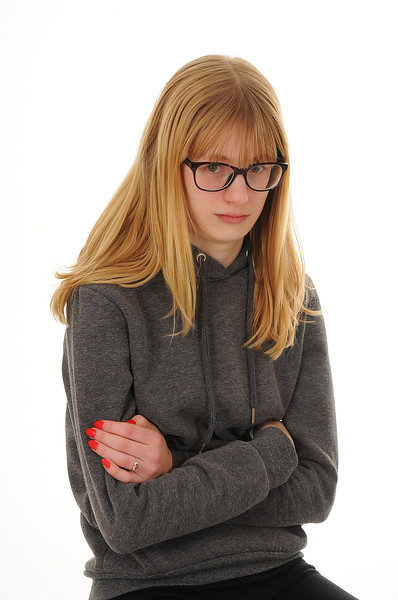pretty blonde teenage girl wearing glasses, looking annoyed, isolated on white background