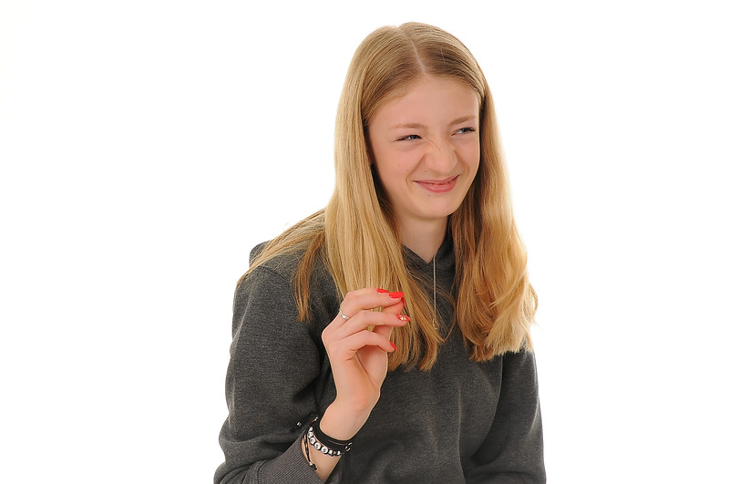 pretty blonde teenage girl wrinkling her nose, isolated on white background