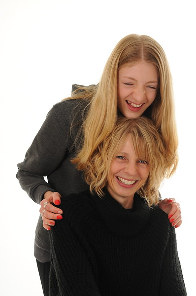 pretty blonde Mum and teenage girl cuddling and laughing, isolated on white background