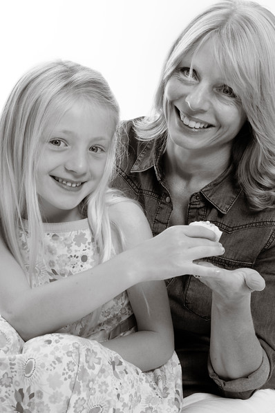 pretty blonde girl and her mum having a cake, isolated on white background