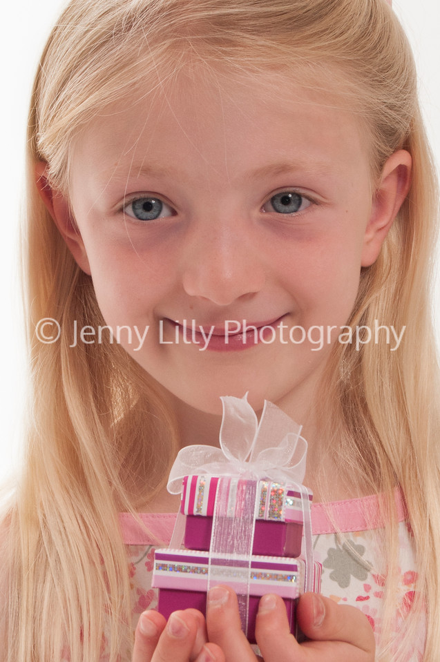 pretty blonde girl holding a stack of presents, tied in a bow, isolated on white background