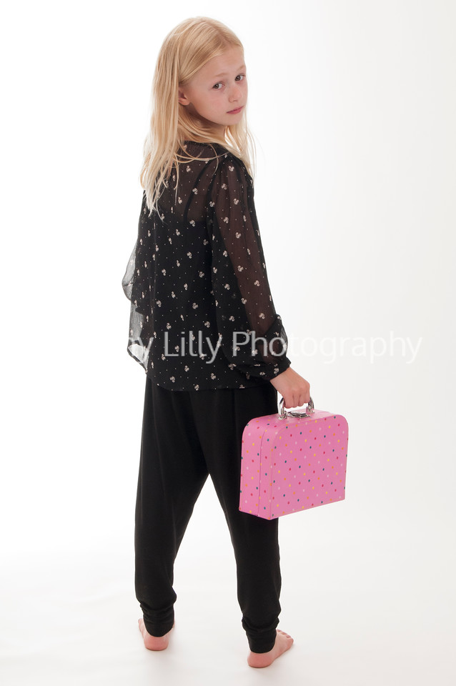 pretty blonde sad girl with a pink suitcase, isolated on white background