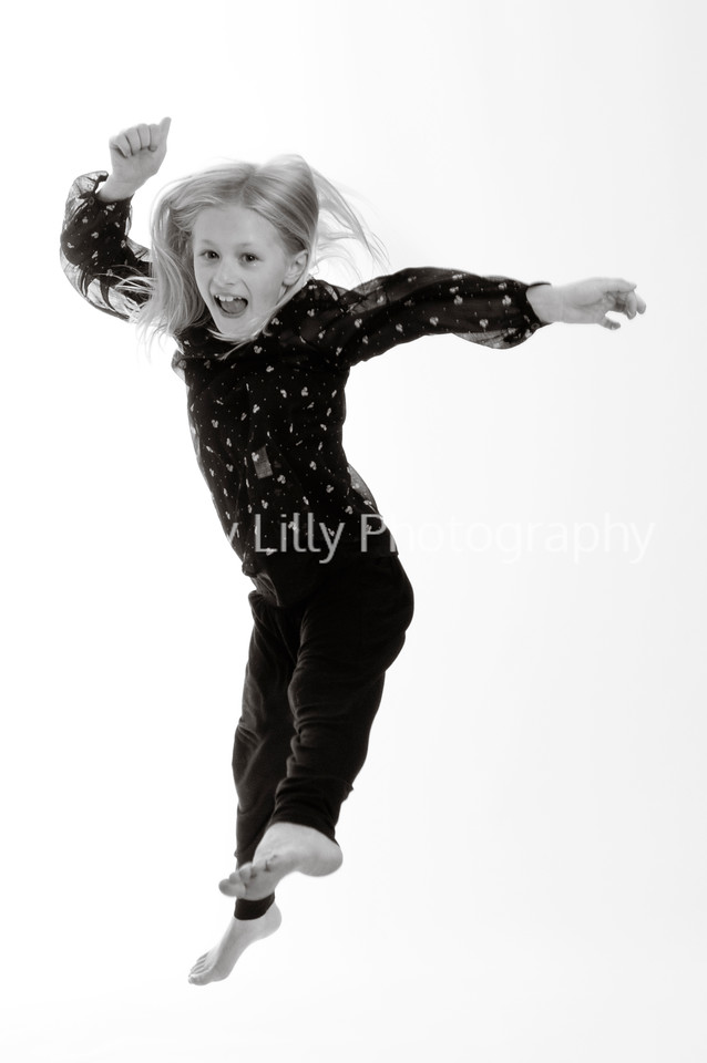 pretty blonde girl jumping with happiness, isolated on white background