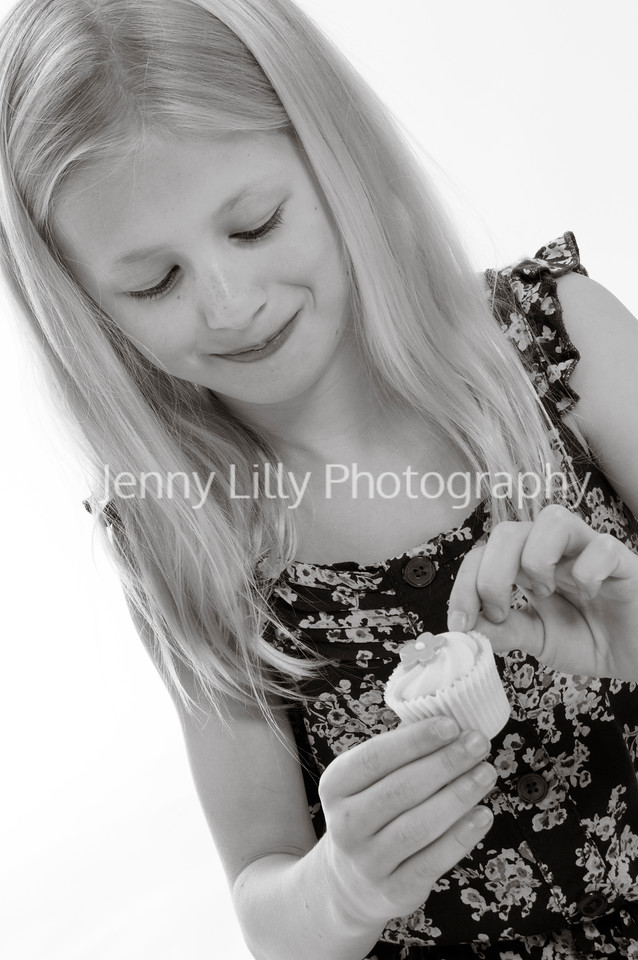 pretty blonde girl unwrapping and eating a fairy cake, isolated on white background