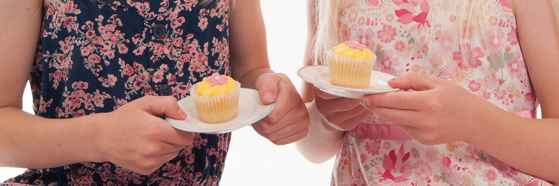 close up of two children with fairy cakes on plates, isolated on white background
