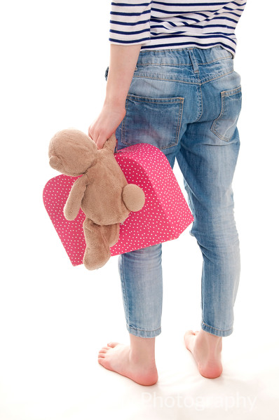 pretty blonde girl holding her teddy bear behind her back isolated on white background