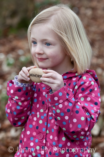 pretty blonde girl with engraved message stone in woods full of snowdrops