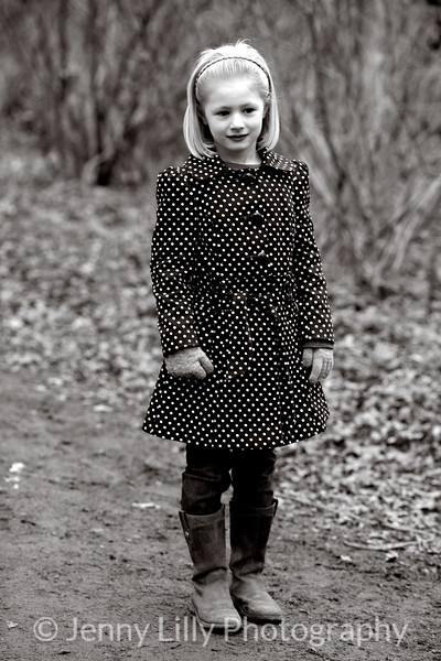 pretty blonde girl walking in the woods in a spotty raincoat, in black and white