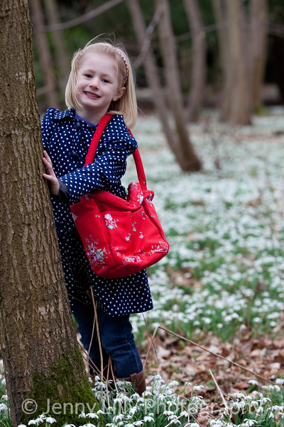 pretty child leaning on a tree in woods of snowdrops