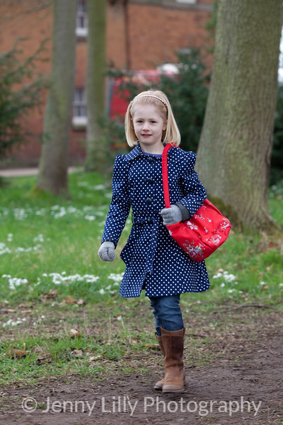 pretty child walking in woods of snowdrops