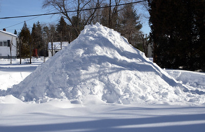 A pile of snow with a huge hole inside.