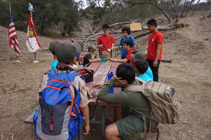 Christian, Owen, Viet, and Martin going over the methods of starting a campfire without matches with the Cubs.