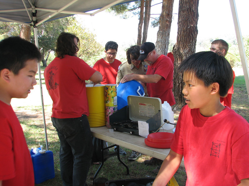 Mr. Pearson fixes a leak in one of the Igloos, while the other boys look on, and Viet discusses lunch plans with Martin.