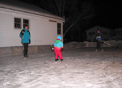 Mrs. Reichenberg, Anna and Mike at the backyard skating rink, January 2003.