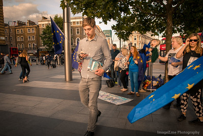 A young man walk by an anti-Brexit protest at Kingscross Station.