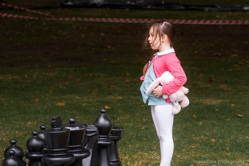 A girl standing at a life size checkerboard outside US Embassy at London