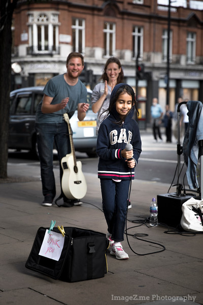 A kid take the stage of a couple performing street music in London, singing Let It Go and attracted a large crowd. Capture the moment of she being a bit shy while taking a bow in the end.