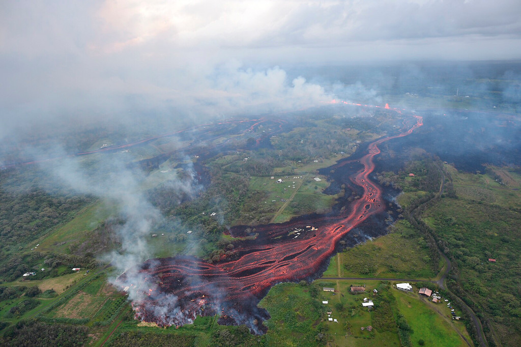 . In this Saturday, May 19, 2018, released by the U.S. Geological Survey, lava emerges from fissures near Pahoa, Hawaii. Kilauea volcano began erupting more than two weeks ago and has burned dozens of homes, forced people to flee and shot up plumes of steam from its summit that led officials to distribute face masks to protect against ash particles. (U.S. Geological Survey via AP)