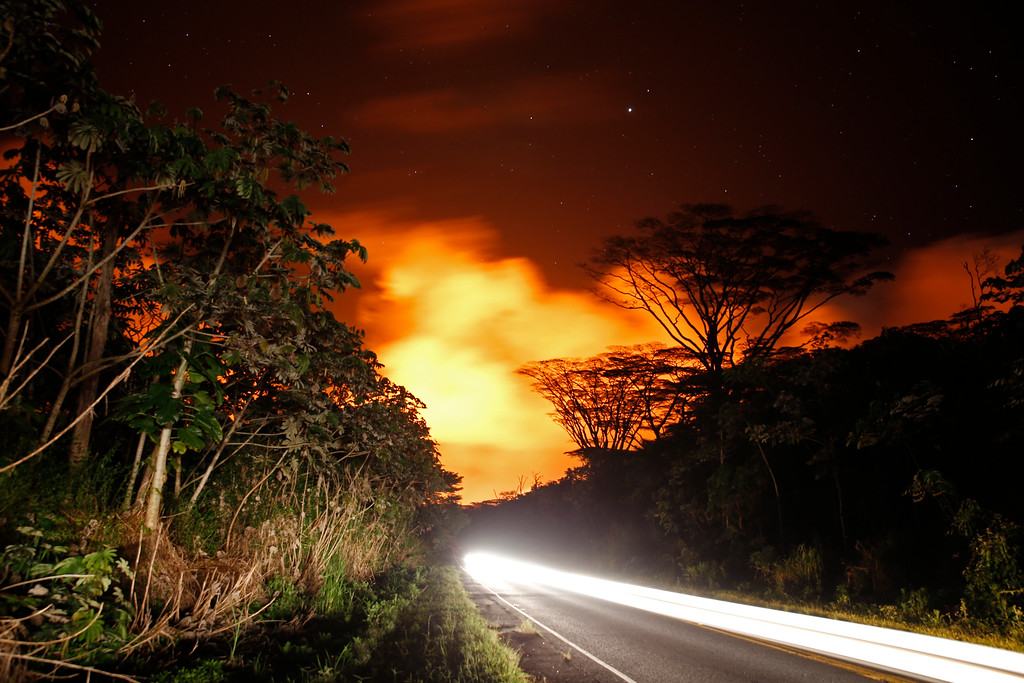 . As lava activity erupts in the background, cars drive down Hwy 132, Friday, May 18, 2018, near Pahoa, HI. (AP Photo/Marco Garcia)
