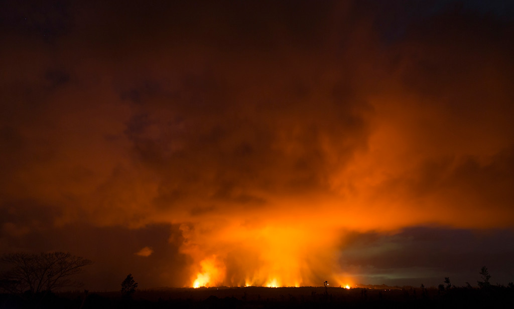 . Volcanic activity from the Malama Ki and Leilani Estates neighborhoods glows from Hwy 137, Thursday, May 17, 2018, near Pahoa, HI. (AP Photo/Marco Garcia)
