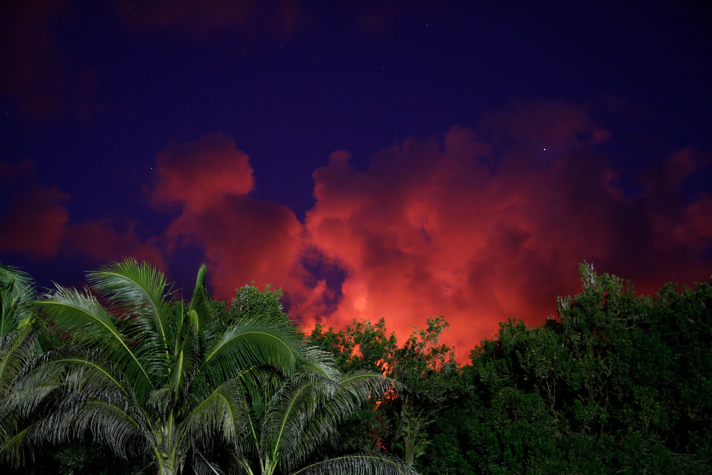 . Clouds turn red from lava flow in the Leilani Estates subdivision near Pahoa, Hawaii, Friday, May 18, 2018. Hawaii residents covered their faces with masks after a volcano menacing the Big Island for weeks exploded, sending a mixture of pulverized rock, glass and crystal into the air in its strongest eruption of sandlike ash in days. (AP Photo/Jae C. Hong)