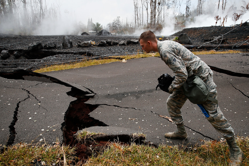 . U.S. Air National Guardsman John Linzmeier looks at cracks as toxic gases rise near by in the Leilani Estates subdivision near Pahoa, Hawaii Friday, May 18, 2018. Hawaii residents covered their faces with masks after a volcano menacing the Big Island for weeks exploded, sending a mixture of pulverized rock, glass and crystal into the air in its strongest eruption of sandlike ash in days. (AP Photo/Jae C. Hong)