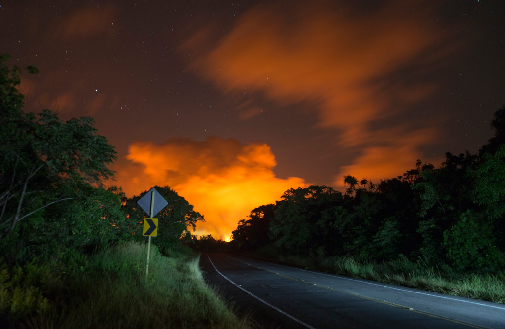 . Volcanic activity from the Malama Ki and Leilani Estates neighborhoods glows in the distance from Hwy 137, Thursday, May 17, 2018, near Pahoa, Hawaii. (AP Photo/Marco Garcia)