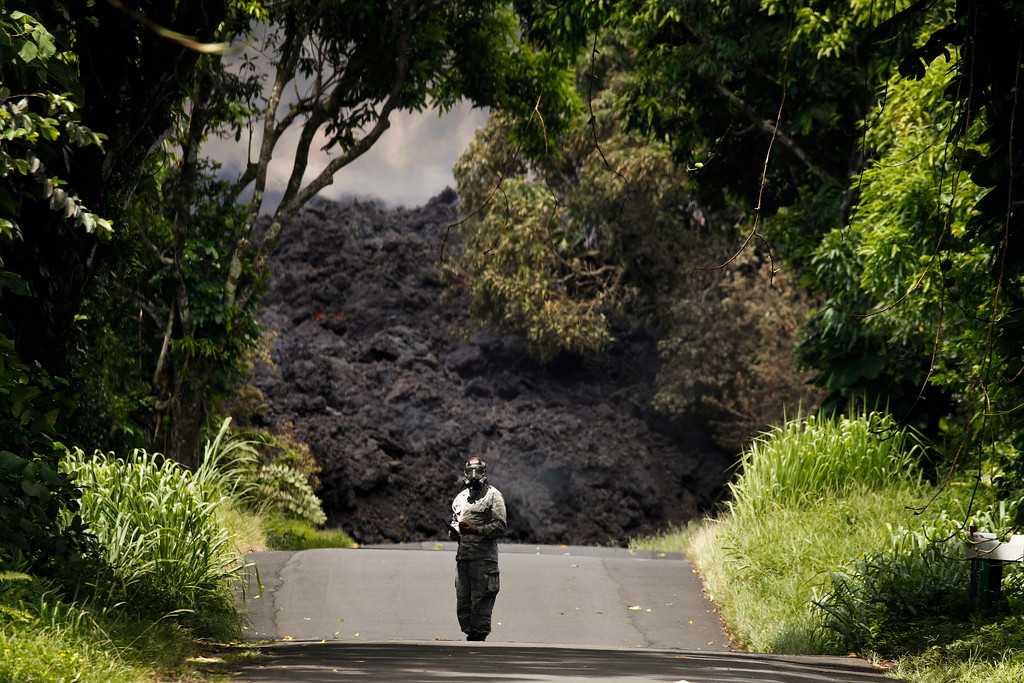 . U.S. Air Force Lt. Col. Chuck Anthony stands near a wall of lava entering the ocean near Pahoa, Hawaii, Sunday, May 20, 2018. Kilauea volcano, oozing, spewing and exploding on Hawaii\'s Big Island, has gotten more hazardous in recent days, with rivers of molten rock pouring into the ocean and flying lava causing the first major injury. (AP Photo/Jae C. Hong)