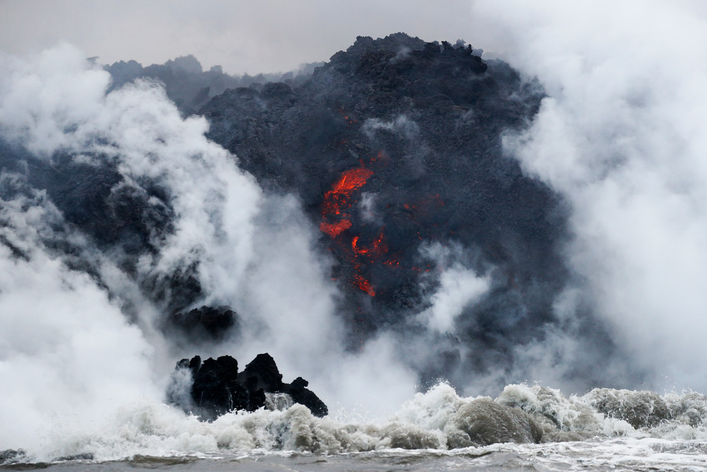 . Lava flows into the ocean near Pahoa, Hawaii Sunday, May 20, 2018. Kilauea volcano that is oozing, spewing and exploding on Hawaii\'s Big Island has gotten more hazardous in recent days, with rivers of molten rock pouring into the ocean Sunday and flying lava causing the first major injury. (AP Photo/Jae C. Hong)