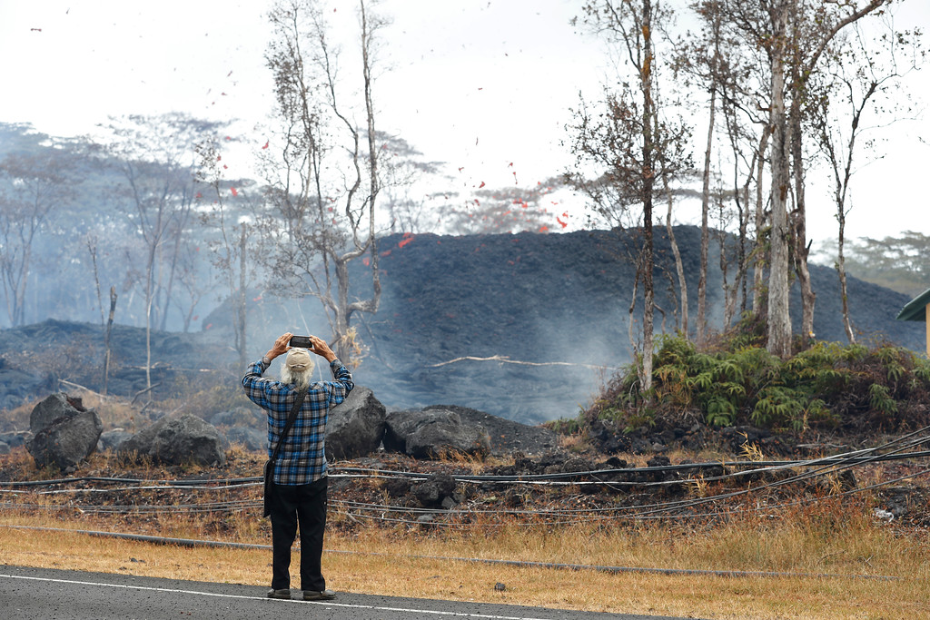 . Edwin Montoya films as the lava shoots out of a fissure on Pohoiki Rd, Friday, May 18, 2018, near Pahoa, Hawaii. Montoya\'s daughter has a farm about a mile away from the lava fissures. The family fears the lava will destroy their farm. (AP Photo/Marco Garcia)