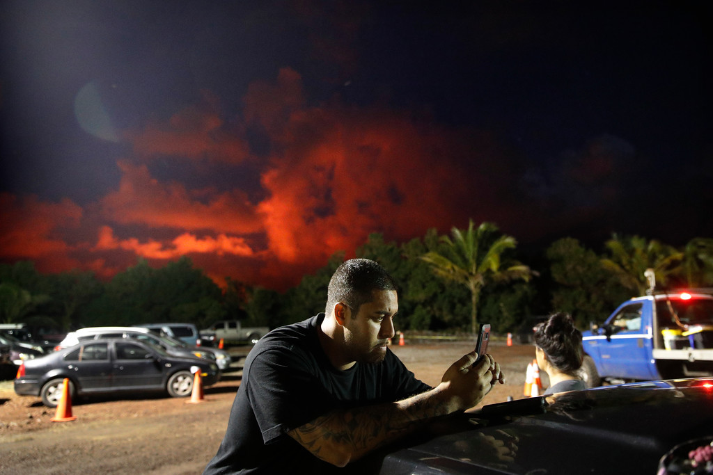 . Evacuee Michael Hauanao, 32, watches a clip on a phone showing volcano activities at a makeshift donation center as clouds turn red from lava flow in the Leilani Estates subdivision near Pahoa, Hawaii Friday, May 18, 2018. Hawaii residents covered their faces with masks after a volcano menacing the Big Island for weeks exploded, sending a mixture of pulverized rock, glass and crystal into the air in its strongest eruption of sandlike ash in days. (AP Photo/Jae C. Hong)
