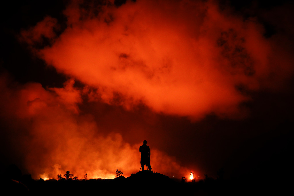 . Peter Vance, 24, photographs lava erupting in the Leilani Estates subdivision near Pahoa, Hawaii Friday, May 18, 2018. Hawaii residents covered their faces with masks after a volcano menacing the Big Island for weeks exploded, sending a mixture of pulverized rock, glass and crystal into the air in its strongest eruption of sandlike ash in days. (AP Photo/Jae C. Hong)